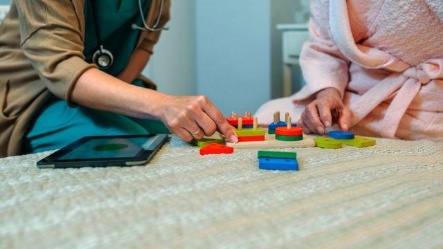 cuidadora fazendo atividade lúdica com paciente