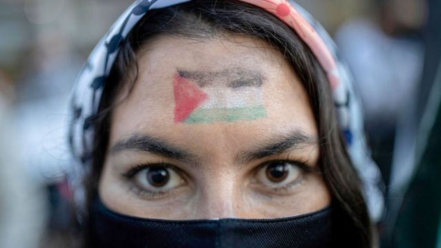A woman of Palestinian origin wears the flag of her country on her forehead.