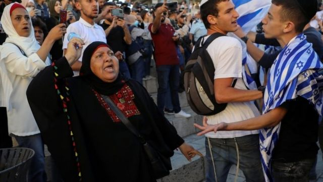 A Palestinian woman argues with Israelis during a flag march in Jerusalem's Old City (15 June 2021)