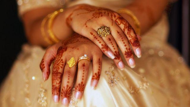 عروس هندية تظهر يديها مزينة بالحناء والمجوهرات