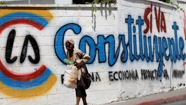 Una mujer camina frente a un grafitti en apoyo a la Constituyente de Venezuela