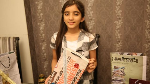 Zymal Umer holds up one of the bags she has made