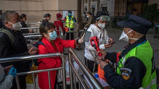 Pessoas mostram seu celular a autoridades na China