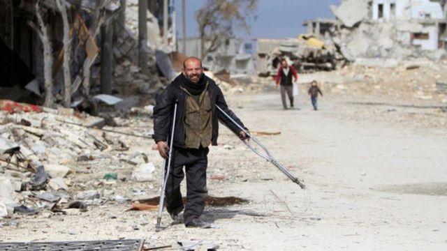 Hombre caminando con muletas en medio de calles destruidas