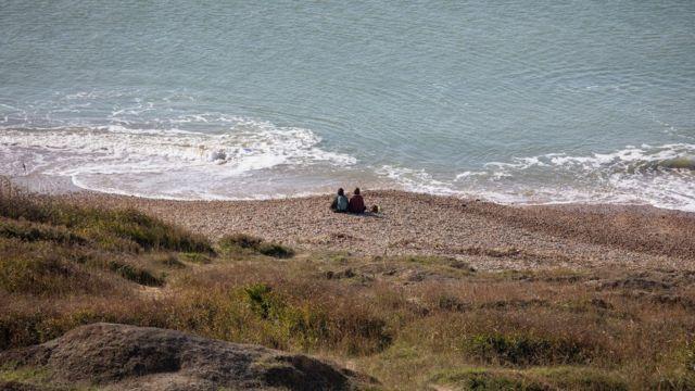 Dos personas sentadas en la costa sur de Inglaterra.
