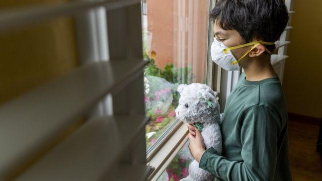 Menino usando máscara olha triste pela janela enquanto segura urso de pelúcia