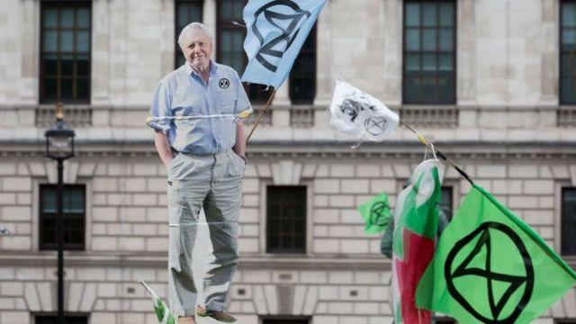 Una imagen de cartón de tamaño natural de David Attenborough es llevada por activistas de Extinction Rebellion durante una protesta en Londres en 2018