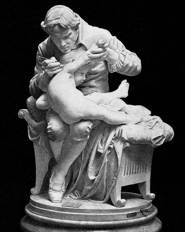 Experimento de Edward Jenner, eternizado nesta estátua vacinando o próprio filho, carrega sérias implicações éticas