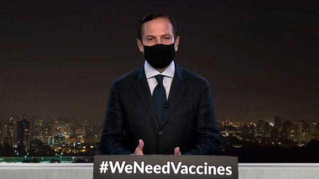 Doria aparece de máscara em frente a palanque com hashtag WeNeedVaccines, com prédios de São Paulo à noite atrás