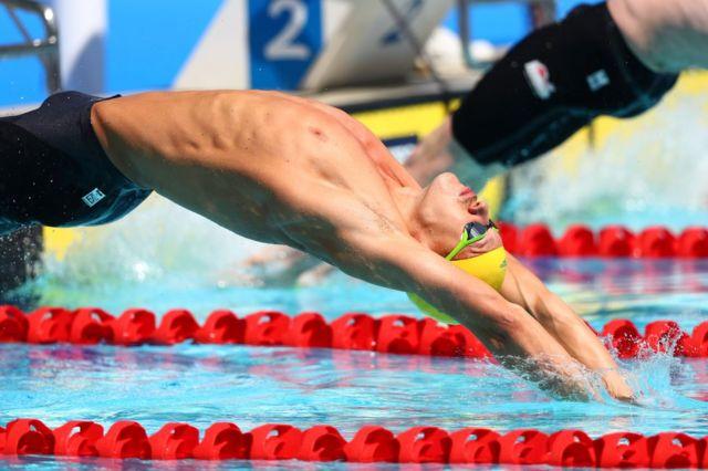 مردوں کے بیک سٹروک 100 میٹر پیراکی کے مقابلے آسٹریلیا کے مچ لرکن الٹی ڈائیو لگائے ہوئے ہوا میں ہیں۔