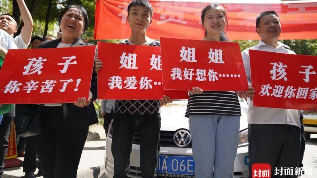 Família que buscou por anos Kang Ying a recebeu com cartazes dizendo 'Bem-vinda de volta, filha' e 'Irmã, senti muito sua falta'