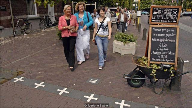 Cruzes brancas nas calçadas, indicando 'NL' de um lado e 'B' no outro