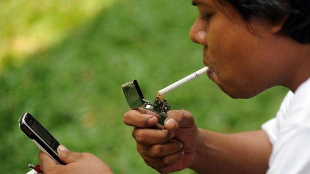 رجل يشعل سيجارة