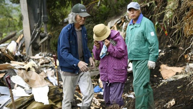 Residents of Atsuma standing next a collapsed house