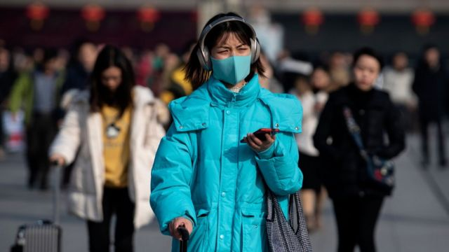 A woman wears a blue face mask as she wheels luggage