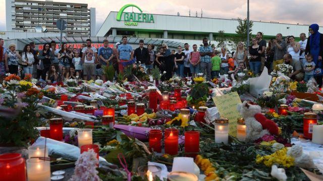 乱射事件のあったショッピングセンター前に、花やろうそくが次々に手向けられた(24日)