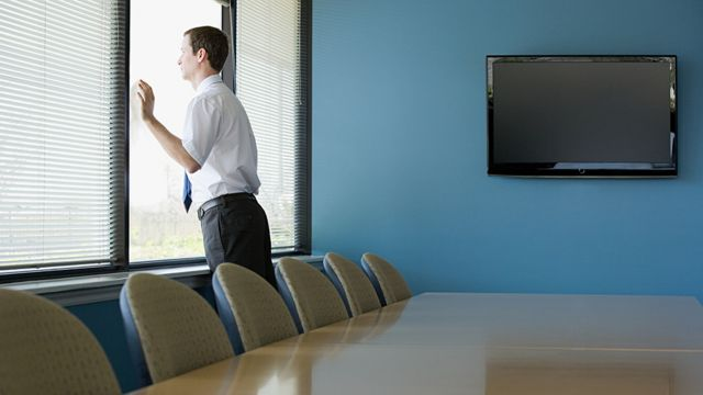 Homem branco olha através de janela de escritório