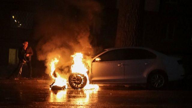 Homem tenta apagar fogo em carro pertencente à embaixada russa na Ucrânia