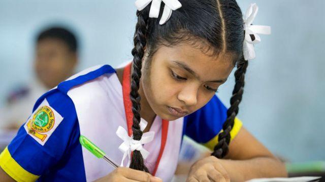 Una estudiante completa un examen de educación primaria en Daca, noviembre 2019