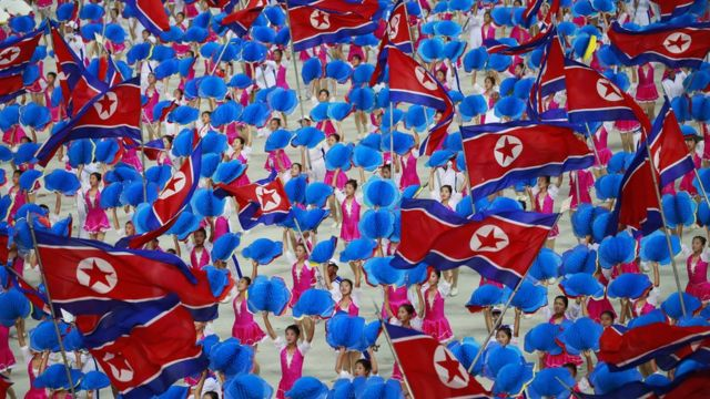 Dancers waving North Korean flags
