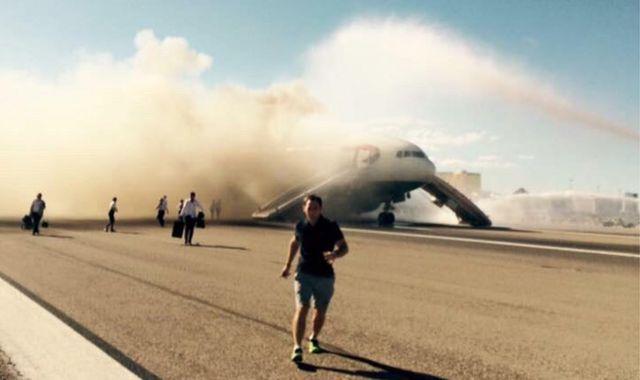 A passenger runs as the smoke billows from the plane 9 September 2015