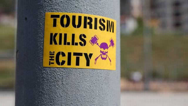 西班牙巴塞罗那一个电灯杆上贴出的反旅游业标语:旅游扼杀城市。