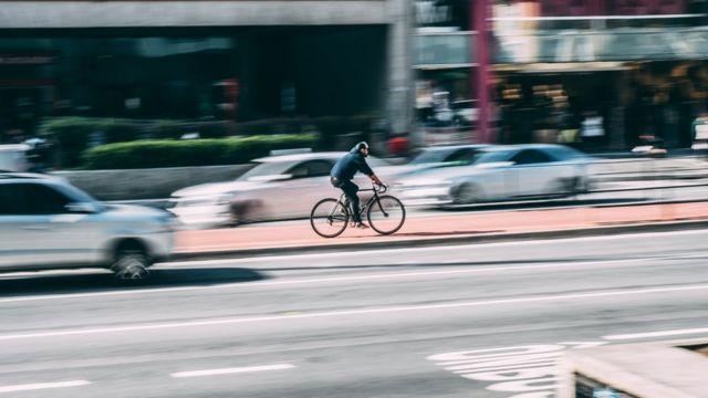Homem pedala na cidade