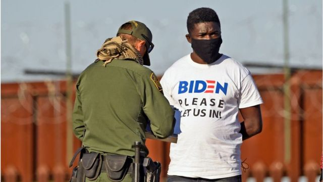 """在亚利桑那州被捕的一名男子身穿印有""""拜登,请让我们进来""""字样的T恤。(photo:BBC)"""