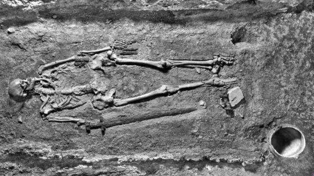 Esta imagen de 1928 muestra el esqueleto tal como se encontró: con un cubo (abajo a la derecha), espada, cuchillos y otros implementos.