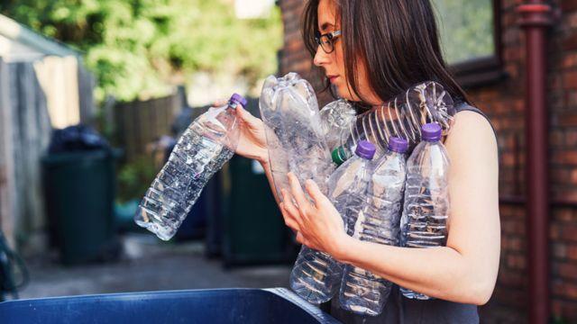 elinde plastik şişeler olan bir kadın