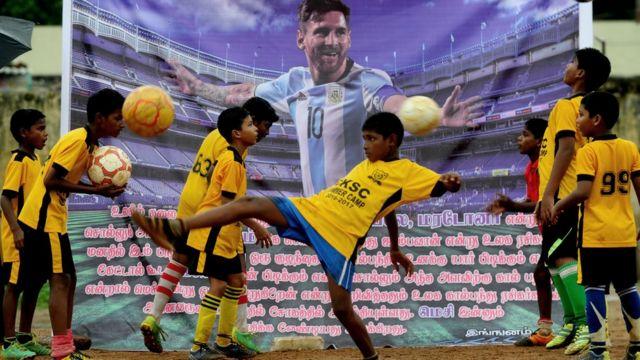 Un grupo de niños juega rente a un retrato de Messi