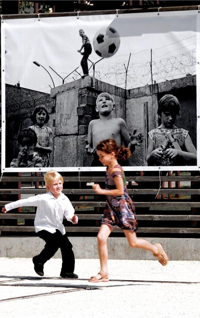 التقط دانيل غواردفسكارو هذه الصورة لطفلين يلهوان أمام صورة قديمة لأطفال يلهون أمام سور برلين.