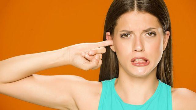 Woman lying her finger in her ear