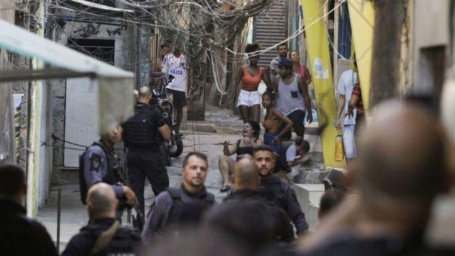 Moradores chora enquanto são observados por policiais