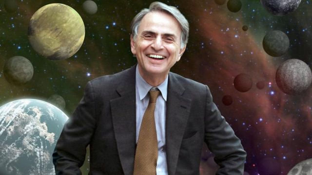 Carl Sagan con ilustración de planetas detrás suyo.