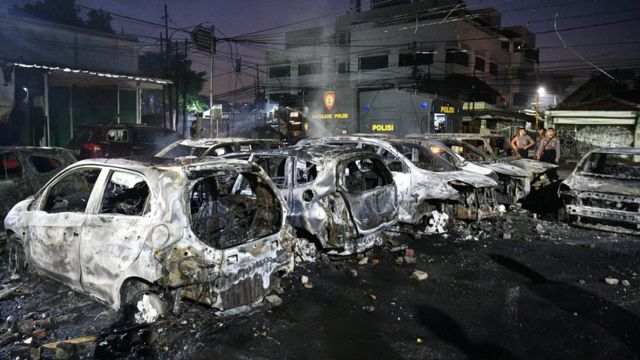 Police officers inspect the damage after cars were set on fire at Brimon (Mobile Police) Dormitory Complex