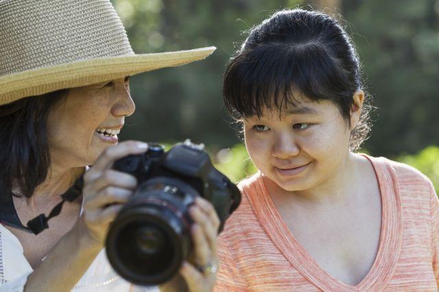 Mulher mostra foto para filha com autismo