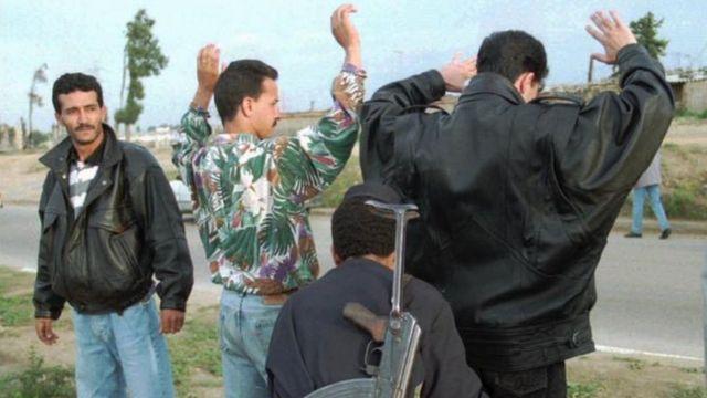 Personas siendo registradas por la policía argelina en 1995.