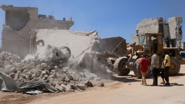 A bulldozer clears the rubble of a building destroyed by government bombardment on the rebel-held town of Urum al-Kubra, Syria (11 August 2018)