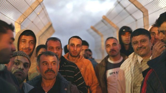 Trabajadores palestinos esperan pasar un puesto de control
