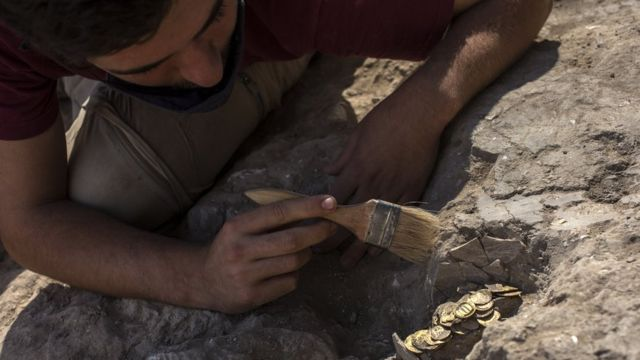 Volunteer Oz Cohen brushes away dust from gold coins found at an archaeological dig in central Israel (18 August 2020)