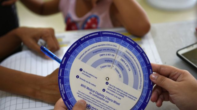 Una madre llena un formulario para un programa de anticoncepción en una barrio pobre de Manila, octubre 2017