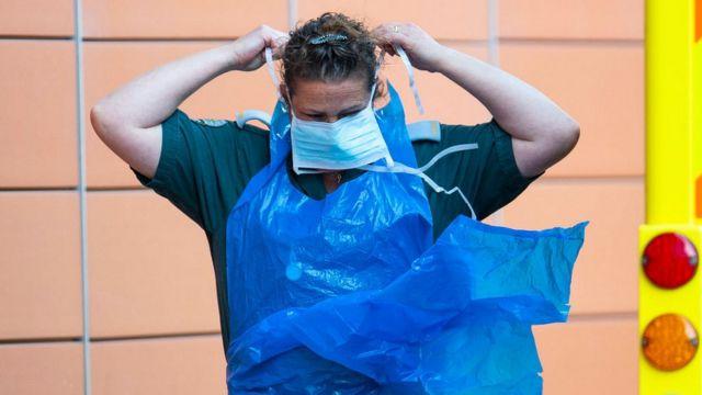 Работник скорой помощи в Британии надевает защитную маску