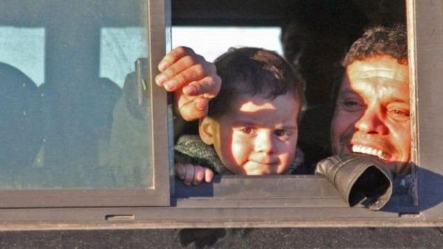 طفل يغادر المدينة ويلقي نظرة على منزله في شرق حلب
