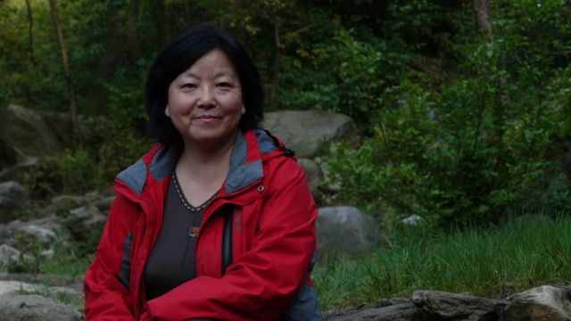 Chinese writer Fang Fang poses in red coat outside.