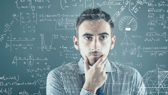 Homem com a mão no queixo, em frente a um quadro com problemas matemáticos