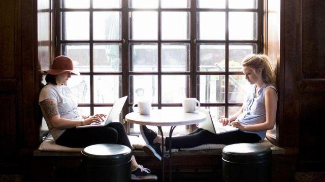 kafede bilgisayar kullanan iki kadın