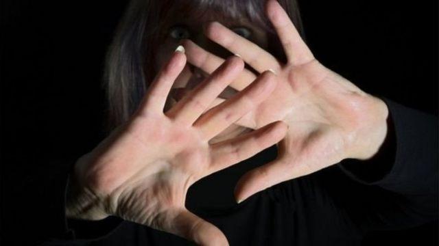 हाथों से चेहरा छिपाती एक औरत