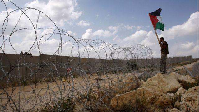 فلسطيني يحمل علم بلاده في مواجهة جنود يقفون على الجدار العازل