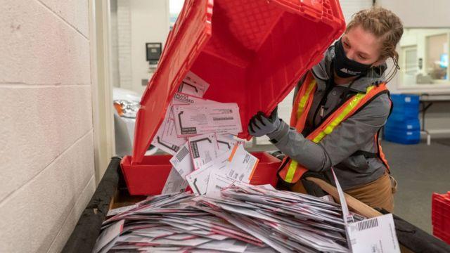 Una trabajadora postal con una cesta llena de votos por correo.